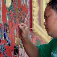 A worker touches up the paint at the Wat Xieng Thong temple in Luang Prabang, Laos. | AP