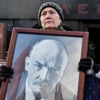 A Russian Communist Party supporter carries a portrait of late Soviet leader Vladimir Lenin as she takes part in a memorial ceremony to mark the 92nd anniversary of his death in Red Square, central Moscow, on Thursday. | AFP-JIJI