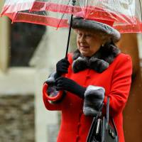 Britain's Queen Elizabeth II shelters under an umbrella as she leaves, after attending the British royal family's traditional Christmas Day church service at St. Mary Magdalene Church in Sandringham, England, Dec. 25. | AP