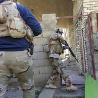 Iraqi security forces clear houses of Islamic State fighters in Ramadi, 70 miles (115 km) west of Baghdad, Sunday. Ramadi, once home to 500,000 people, lies largely in ruins after months of air bombardment and the scorched-earth practices of Islamic State fighters in retreat. The U.S-led coalition acknowledges the importance of rebuilding, but actual money for the effort falls far short. | AP