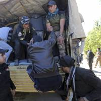 Iraqi soldiers help trapped civilians board a vehicle that will take them to a safer place Thursday in Ramadi, Iraq. | AP