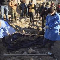 Iraqi forensic team members work at the site of a mass grave believed to contain the bodies of Iraqi civilians killed by Islamic State group militants in Ramadi, 115 km (70 miles) west of Baghdad Monday. | AP