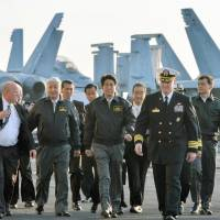 Prime Minister Shinzo Abe and Defense Minister Gen Nakatani (second from left) are given a tour of the nuclear-powered aircraft carrier USS Ronald Reagan in Sagami Bay, off Kanagawa Prefecture, in October. | KYODO