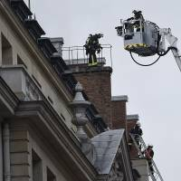Firefighters work on extinguishing a fire at the Ritz Carlton Hotel in Paris on Tuesday. The landmark hotel is currently closed for renovations. | AFP-JIJI