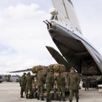 Russian air force personnel prepare to load humanitarian cargo on board a Syrian plane at Hemeimeem air base in Syria Wednesday. | AP