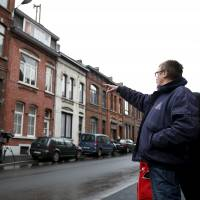 A resident points at a house located in a street called Rue du Fort in Charleroi, Belgium, Wednesday. A number of the Paris attackers used two apartments and a house in Belgium as possible safe houses in the weeks in leading up to their coordinated shooting and suicide bomb assault on the French capital, investigators said on Wednesday. | REUTERS