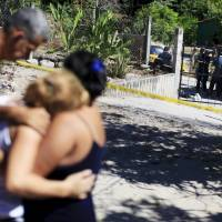 Relatives react as police investigators and forensic experts work at a crime scene where five men were killed in the town of Olocuilta, El Salvador, Friday. The five gang members died in a shootout with police, an official said. | REUTERS