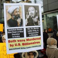 Demonstrators hold signs during a rally against the execution of Shiite cleric Sheikh Nimr al-Nimr in Saudi Arabia, in New York Sunday. | REUTERS