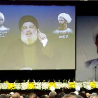 Lebanon's Hezbollah leader, Sayyed Hassan Nasrallah, addresses his supporters via a screen during a memorial service to mourn the death of Sheikh Mohammad Khatoun who was a member of Hezbollah Central Council, and to condemn the execution of Sheikh Nimr al-Nimr, a Shiite cleric who was executed along with others in Saudi Arabia, in Beirut's southern suburbs Sunday. Nasrallah said on Sunday Saudi Arabia's execution of Nimr was a 'message of blood' and Riyadh sought to create sectarian strife across the world. | REUTERS