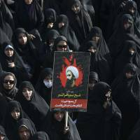 A woman in Tehran on Monday holds up a poster showing Sheikh Nimr al-Nimr, a prominent Saudi Shiite cleric executed last week by Saudi Arabia. | AP