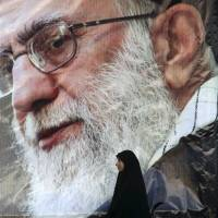 An Iranian woman stands beneath a portrait of Supreme Leader Ayatollah Ali Khamenei after a rally in Tehran on Monday in protest at the execution by Saudi Arabia of prominent Shiite cleric Sheikh Nimr al-Nimr. | AP