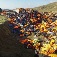 A man unloads a truck filled with life Jackets at the garbage area in the mountains of Lesbos Island, Greece, Monday.   AP