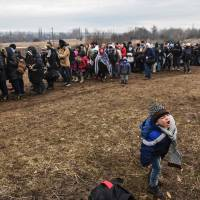 A young boy yells as migrants and refugees wait in line for a security check after crossing the Macedonian border into Serbia, near the village of Miratovac, on Tuesday. | AFP-JIJI