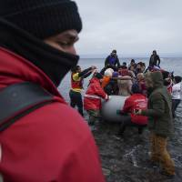 Members of the Greek Red Cross and other volunteers help migrants and refugees to disembark from an inflatable boat after crossing the Aegean sea from Turkey to the Greek island of Lesbos, on Tuesday. | AP