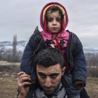 A man carries a child as migrants and refugees wait in line for security check after crossing the Macedonian border into Serbia, near the village of Miratovac, on Tuesday. | AFP-JIJI