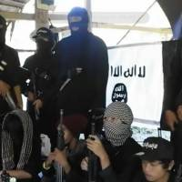 Gunmen line up in front of the Islamic State flag in this grab from an online video purportedly shot in the southern Philippines. An Arabic title on the video describes the troops as 'soldiers of the caliphate in the Philippines.'