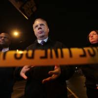 Seattle Mayor Ed Murray speaks with reporters Tuesday at the scene of a fatal shooting at a homeless encampment in Seattle. | DEAN RUTZ / THE SEATTLE TIMES VIA AP