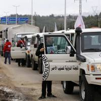 Aid vehicles wait on the outskirts of besieged rebel-held Syrian town of Madaya on Monday. Dozens of aid trucks headed to Madaya, where more than two dozen people are reported to have starved to death, after an outpouring of international concern and condemnation over the dire conditions in the town, where some 42,000 people are living under a government siege. | AFP-JIJI