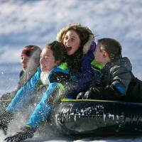 Julia Hunt (bottom), 12, and Kayla Hunt, 9, slide down a hill together with their friends in Park Ridge, New Jersey, Sunday. | KEVIN R. WEXLER / THE RECORD OF BERGEN COUNTY VIA AP