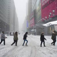 Pedestrians make their way across snow covered Broadway Saturday in New York. | AFP-JIJI