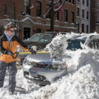 A man clears his car with a shovel near Central Park on Sunday in New York. | AFP-JIJI