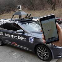 A researcher from the Intelligent Vehicle IT Research Center at Seoul National University shows a smartphone application that commands the Snuber driverless car in Seoul on Tuesday. The device on the vehicle's roof scans the road. The university is testing the sedan that can pick up and transport passengers without a human driver. | AP