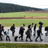 Migrants walk into Germany after crossing the border from Austria near the village of Wegscheid in November.  |  AFP-JIJI