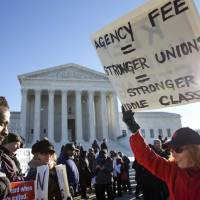 Lesa Curtis (right) of Westchester, New York, who is pro agency fees and a former president of her union, rallies outside of the Supreme Court in Washington, Monday as the court heard arguments in the 'Friedrichs v. California Teachers Association' case. The justices were to hear arguments in a case that challenges the right of public-employee unions to collect fees from teachers, firefighters and other state and local government workers who choose not to become members. | AP