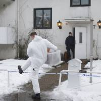 A forensic police officer carries a box of evidence following a search in front of a migrant center in Molndal outside Goteborg, Sweden, Monday. A female employee was killed in a knife attack inside the migrant center. | AP