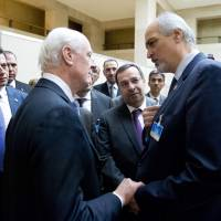 Syrian Ambassador to U.N. Bashar al-Jaafari (right), head of the government delegation to Syrian peace talks, is greeted by U.N. envoy for Syria Staffan de Mistura upon his arrival at the opening of the talks at the United Nations Offices in Geneva on Friday. | AFP-JIJI