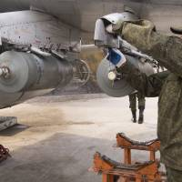 A Russian air force technician attaches a bomb to a Russian ground attack jet at Hemeimeem air base in Syria on  Jan. 20.   AP