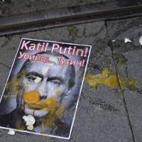 A picture of Russian President Vladimir Putin is splattered with eggs during an October protest in Istanbul. The slogan, in Turkish and Russian, reads 'Murderer Putin' | AP