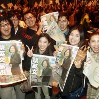 Supporters of Democratic Progressive Party leader Tsai Ing-wen show newspapers reporting on her victory outside the DPP campaign headquarters on Saturday in Taipei. | AP