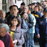 A police officer patrols outside a polling station as residents line up to vote in the Xindian district of New Taipei City on Saturday | AFP-JIJI