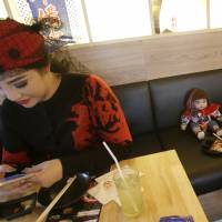 Supavadee Tapmalai uses her smartphone next to a 'child angel' doll at a Japanese restaurant in Bangkok on Friday. | AP