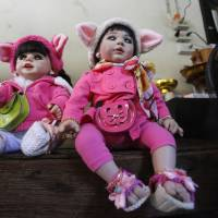 'Child angel' dolls sit on a chair in Bangkok on Thursday. Thailand. Thais are known for being superstitious, and the doll phenomenon has been analyzed as a modern version of a traditional totem containing real body parts, but as a fad it seems have more in common with Furby dolls. | AP