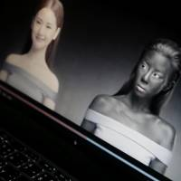 An online advertisement by Thai cosmetics company Seoul Secret showing Thai actress Cris Horwang is displayed on a computer screen in Bangkok on Friday. The company has pulled the video, in which the Thai movie star wears blackface and promotes a skin whitener with the slogan: 'You just need to be white to win.' The company issued a 'heartfelt apology,' saying in a statement that it had no intention to convey racist messages. | AP