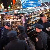 NYPD officers take food from a catering truck provided by the Patrolmen's Benevolent Association during the hours leading up to the annual New Year's Eve celebration in Times Square, Thursday. Nearly 6,000 armed police officers are guarding Times Square as 2015 draws to a close. | AP