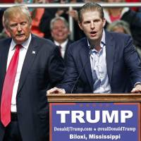 Republican presidential candidate Donald Trump listens as his son, Eric Trump, speaks during a rally in Biloxi, Mississippi, Saturday. | AP