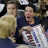 An audience member reacts as U.S. Republican presidential candidate Donald Trump greets her at a campaign rally in Lowell, Massachusetts, on Monday. | REUTERS