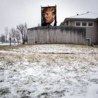 A poster of Donald Trump, president and chief executive of Trump Organization Inc. and 2016 Republican presidential candidate, stands outside of a home as snow falls in West Des Moines, Iowa, on Monday. | BLOOMBERG