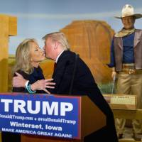 A wax statue of John Wayne watches as Republican presidential candidate Donald Trump kisses John Wayne's daughter, Aissa, during a news conference at the John Wayne Museum on Tuesday in Winterset, Iowa. | AP