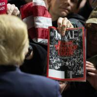 A man holds up a copy of Time magazine as Republican presidential candidate Donald Trump greets members of the audience after speaking at a rally at Muscatine High School in Muscatine, Iowa, Sunday. | AP