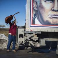 A Trump supporter breaks out his guitar to sing during a Truckers for Trump convoy event for Republican Presidential Candidate Donald Trump in Des Moines, Iowa, Thursday, ahead of the Iowa Caucus. With five days to go before the first vote in the presidential nominations process in Iowa, Trump is dominating the airwaves. His approval rating has never been higher. | AFP-JIJI