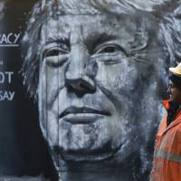 A construction worker stands in front of a piece of street art portraying prospective U.S. Presidential candidate Donald Trump, in east London, Thursday. An online petition to bar Trump from entering the United Kingdom recently triggered a debate in Parliament after if was signed by over 500,000 people. | REUTERS