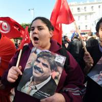The daughter of late Tunisian opposition figure Mohamed Brahmi, who was murdered on July 25, 2013, outside his home by jihadis, holds a placard bearing his portrait Thursday during a rally on Habib Bourguiba Avenue in Tunis to mark the fifth anniversary of the 2011 revolution. | AFP-JIJI