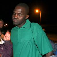 Sudanese migrant Abdul Haroun is greeted by his lawyer and support workers from a nongovernment refugee rights group as he leaves Elmley prison in southern EnglandMonday. A Sudanese man who made global headlines in August when he walked 50 km (30 miles) through the Channel Tunnel from France to England, highlighting the plight of migrants, has been granted asylum in Britain. | REUTERS