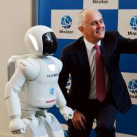 Australian Prime Minister Malcolm Turnbull takes a selfie with Honda Motor Co.'s humanoid robot Asimo at the Miraikan (National Museum of Emerging Science and Innovation) in Tokyo on Dec. 18. | REUTERS