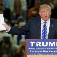 U.S. Republican presidential candidate Donald Trump holds up his notes of a recent poll at a campaign rally in Claremont, New Hampshire, Tuesday. | REUTERS
