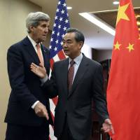U.S. Secretary of State John Kerry greets Chinese Foreign Minister Wang Yi before their bilateral meeting at the Ministry of Foreign Affairs in Beijing on Wednesday. | REUTERS